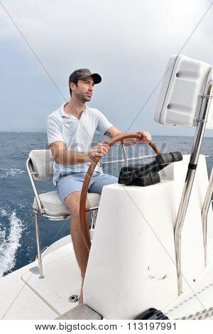 Skipper sitting at sailboat wheel
