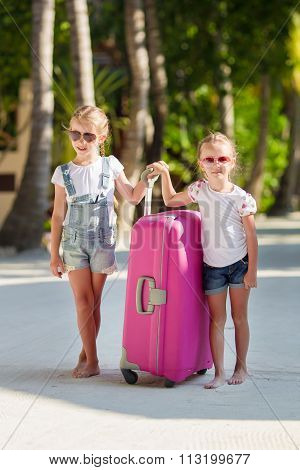 Little adorable girls with luggage during summer vacation