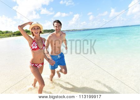 Cheerful couple running on a white sandy beach