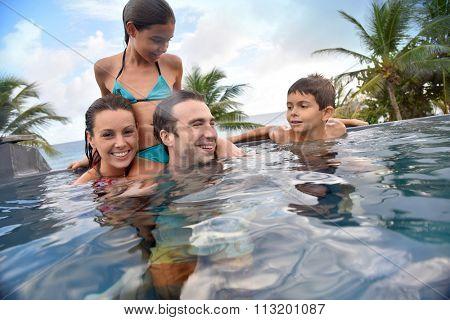 Family of four enjoying swimming-pool