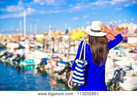 Young beautiful woman walking in port during italian vacation