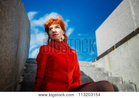 portrait of young redhead woman in red winter coat sitting on steps and looks afar against the blue