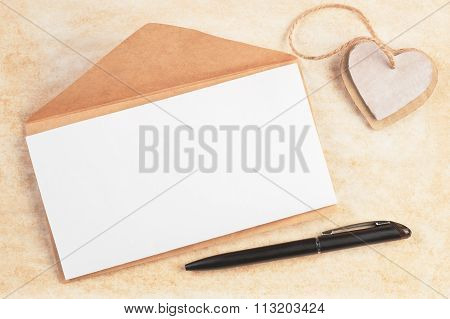 Envelope With Blank Sheet Decorated Cardboard Hearts And Pen On Old Paper Background With Copy Space