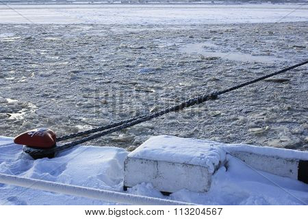 frozen ship cable , old bollard at the pier in winter