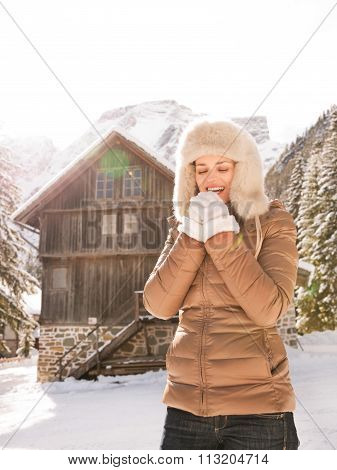 Happy Woman Blowing Warm Breath On Hands Near Mountain House