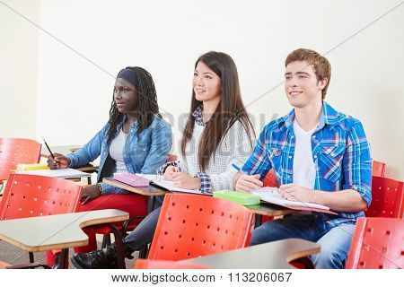 Interracial group of students taking notes in class