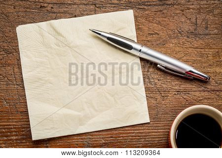 napkin, pen and coffee over grunge wood table, top view