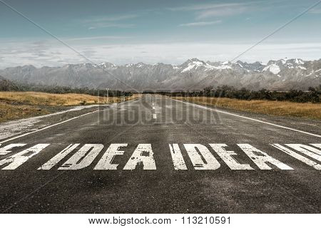 Conceptual image of asphalt road with word idea drawn with paint