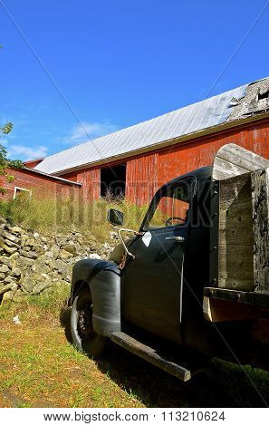Old truck parked by deteriorating red barn