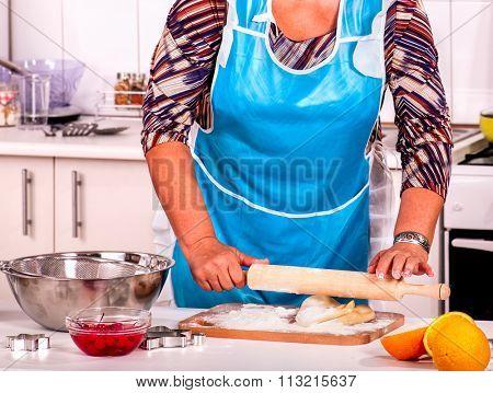 Mature woman  pensioner knead dough at kitchen.