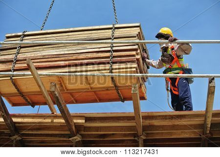 Group of construction workers lifting bundle of timber using mobile crane