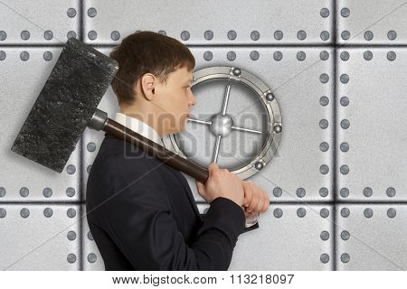 Determined businessman with hammer in hands against the background of the safe