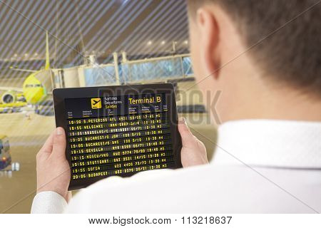 Businessman with tablet in airport with flight schedule and departure and gate information