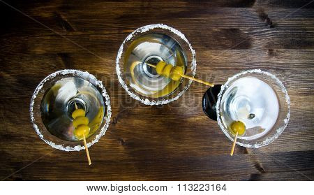 Three Martini With Olives On A Wooden Table.