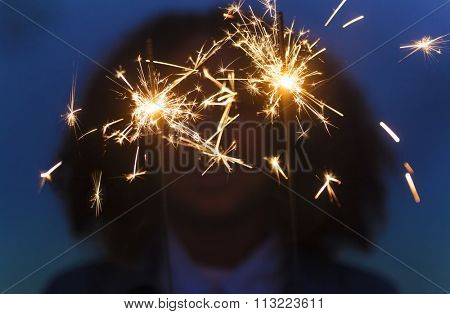 African American young woman teenage girl playing with sparklers at a party