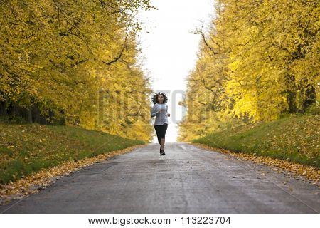 Beautiful mixed race African American young woman girl teenager fitness running jogging in Autumn Fall trees