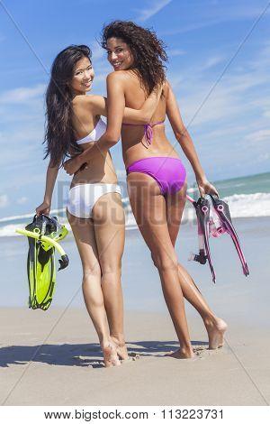 Beautiful young women girls in bikinis with diving equipment on a beach