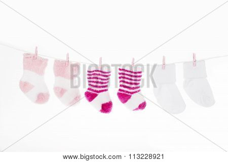 Pink And White Baby Socks On Clothesline, Isolated