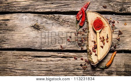 Dried And Ground Red Chili Pepper On Oak Stand.