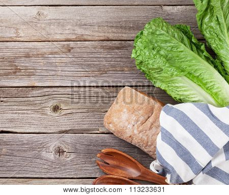 Fresh Romano Caesar salad cooking on wooden table. Top view with copy space