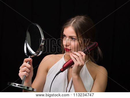 Woman With A Mirror And Flat Hair Iron