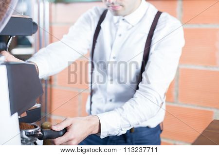Close-up Of Man With Holder Grinding Coffee