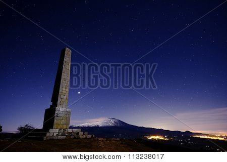 Etna Volcano and Nelson's Obelisk in the night stars from Nebrodi Park in Sicily