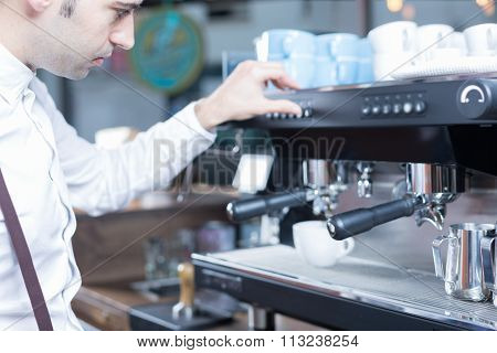 Side View Of Bartender Pushing The Button On Coffee Machine