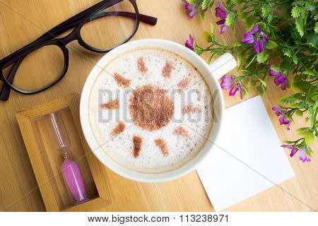 latte art coffee in sun design with papernote and sandglass on wooden table vintage tone