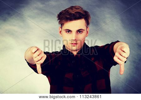 Young upset man showing thumbs down.