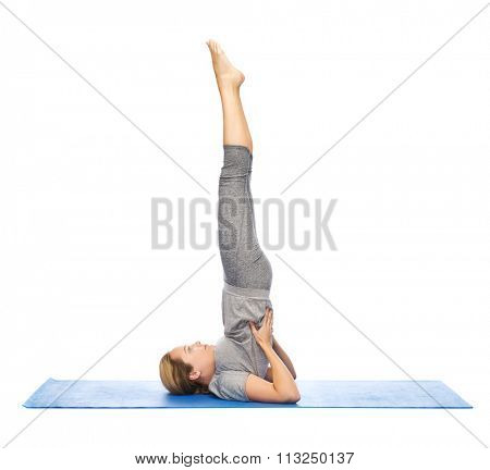 woman making yoga in shoulderstand pose on mat