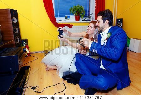 bride and groom playing together videogames with joysticks - gaming and wedding concept.