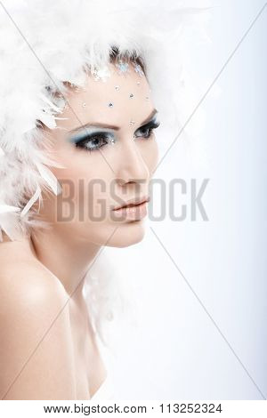 Beauty portrait of winter girl in fancy makeup with rhinestones, daydreaming.