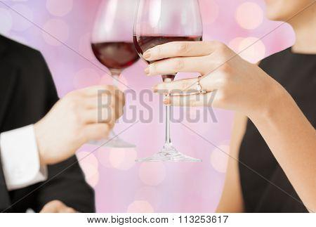 happy engaged couple clinking wine glasses