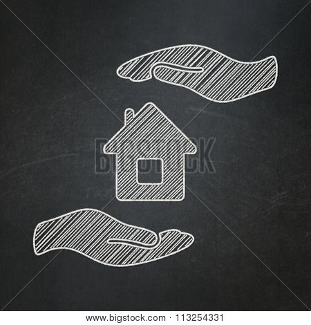 Insurance concept: House And Palm on chalkboard background