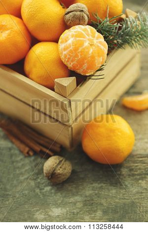 Tangerines in wooden crate, on old wooden table, close up