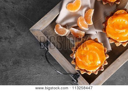 Sweet cakes with tangerines on dark metal table, close up