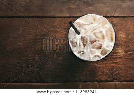 Cup of ice coffee with straw on wooden background