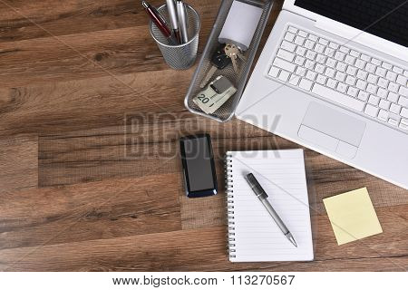 High angle view of a business desk with laptop computer, cell phone, money clip, note pad, paper, pen, pen holder car keys with copy space.