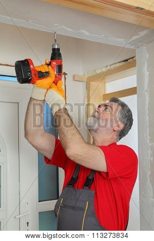 Construction Site, Worker Installing Gypsum Board Using Electric Tool