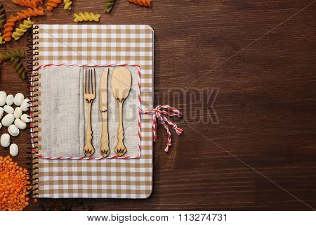 Decorated cookbook on wooden background, copy space