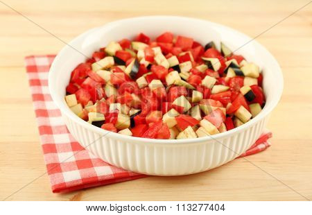 Ratatouille, stewed vegetable dish with tomatoes, zucchini, eggplant before cooking, on wooden background