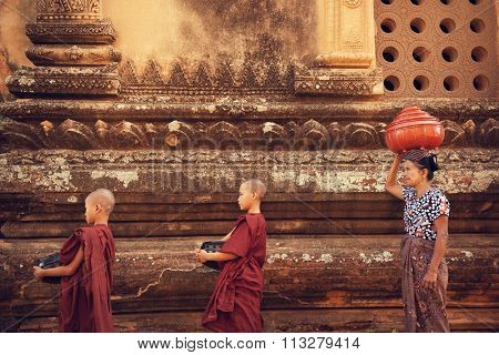 Buddhist novice monks walk to collect alms and offerings at old bagan, Myanmar. This procession is held every morning.