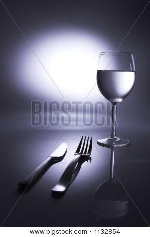 fork kinfe water glass in spotlight table