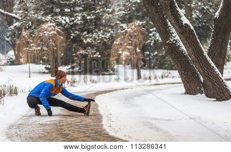 Young sport woman doing exercises during winter training outside in cold snow weather