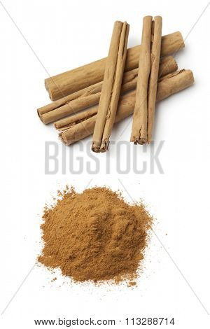 Cinnamon sticks and a heap of ground powder on white background