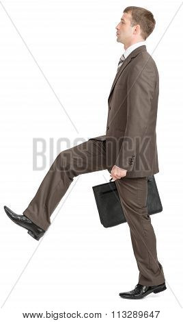 Businessman making large step with suitcase