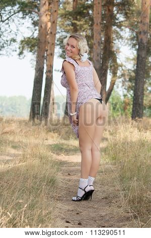 young sexy woman in a mini summer dress showing her legs