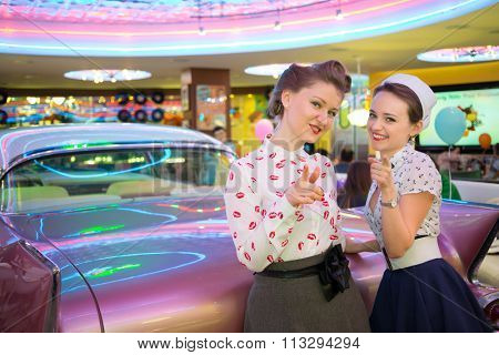 Two beautiful girls in retro dress gesture and have a fun at the bar with pink car, focus on the left girl.