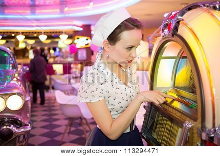 Young woman in retro dress press button of old-fashion musical machine in bar, focus on the machine.